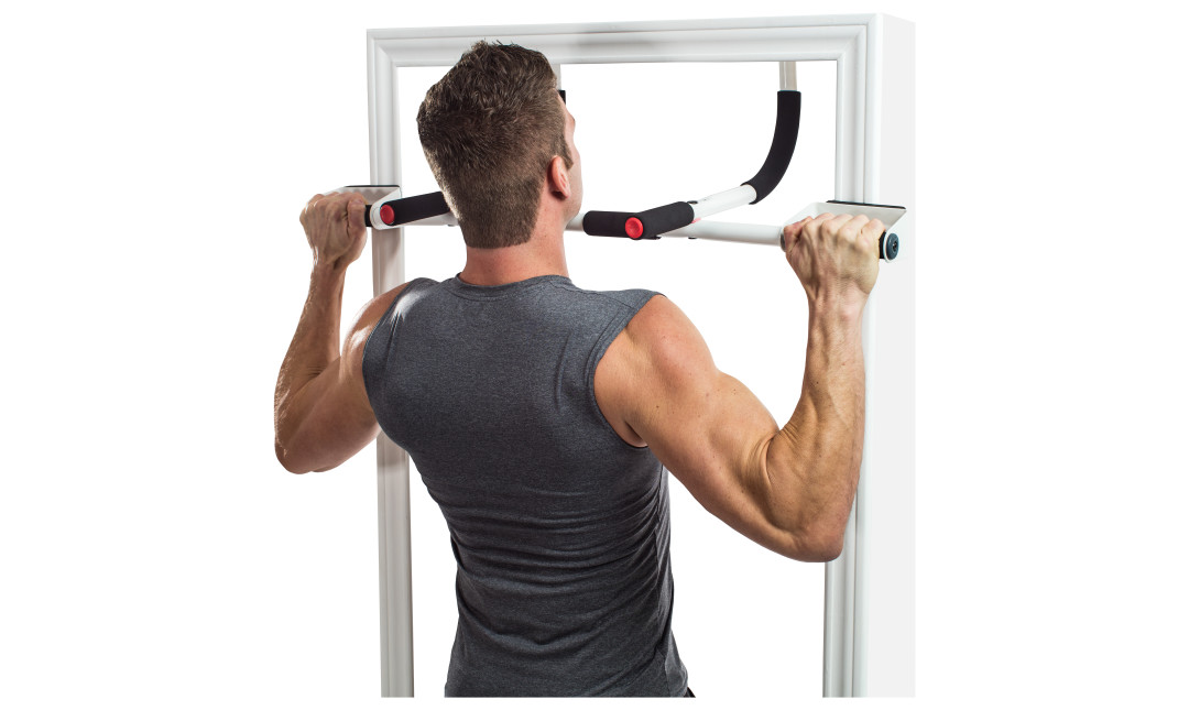 Man in grey shirt facing the opposite direction using the Perfect Multi Gym as a doorway pullup bar hanging from a white door frame with a white background